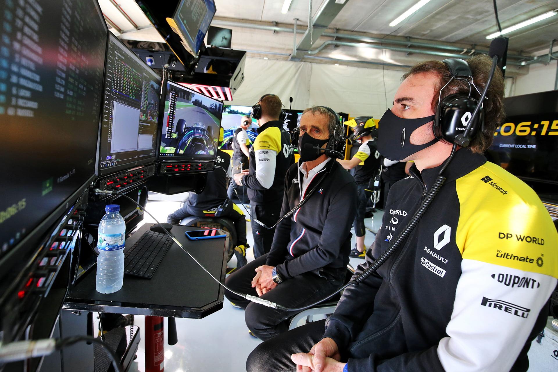 Alain Prost observa los monitores junto a Fernando Alonso.
